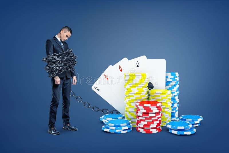 Um homem de negócios triste limitado por uma grande corrente do metal para empilhar de cartões do casino e de microplaquetas colo imagem de stock royalty free