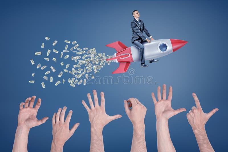Um homem de negócios voa o assento em um foguete que deixe uma cauda do dinheiro com muitas mãos gigantes que tentam a travar imagens de stock royalty free