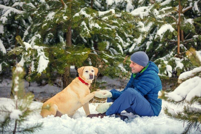 Um homem de sorriso feliz e um cão que sentam-se em uma floresta do inverno imagens de stock