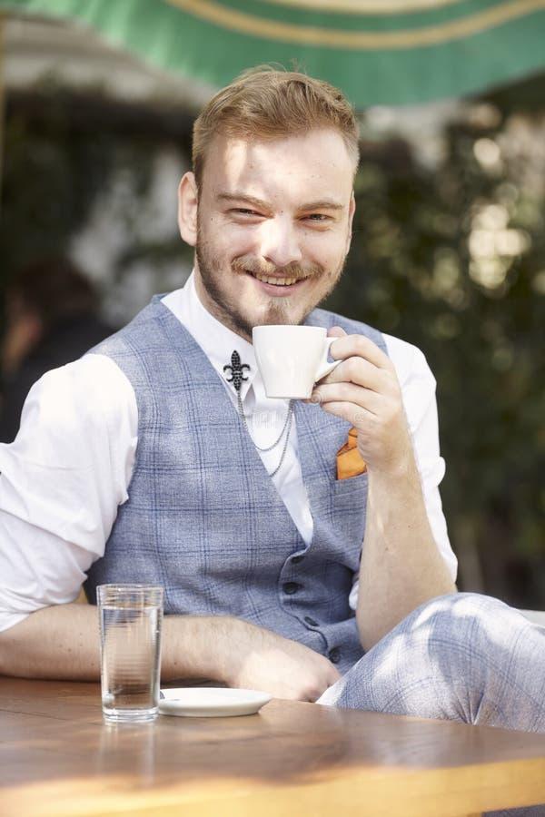 Um homem de sorriso novo, 20-29 anos velho, terno vestindo do moderno, sentando-se na tabela no jardim do café, olhando à câmera, foto de stock royalty free