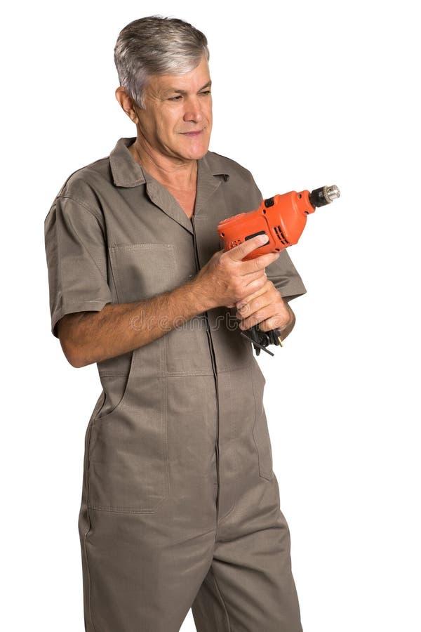 Um homem de sorriso que guarda uma broca de martelo e que olha nos imagens de stock