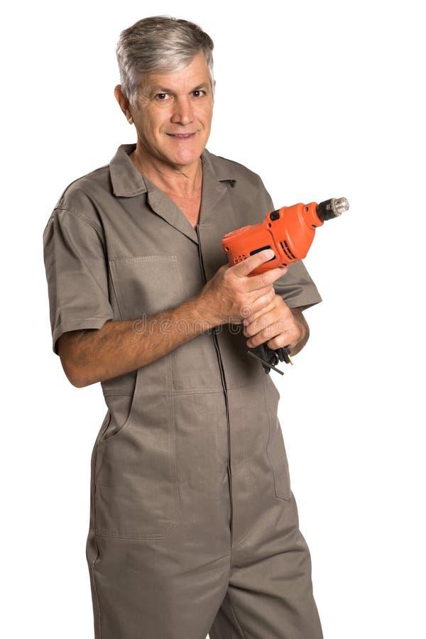 Um homem de sorriso que guarda uma broca de martelo e que olha nos imagem de stock royalty free