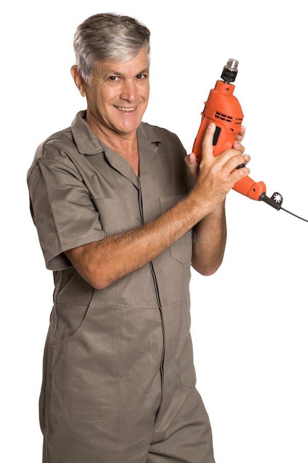 Um homem de sorriso que guarda uma broca de martelo e que olha nos imagens de stock royalty free