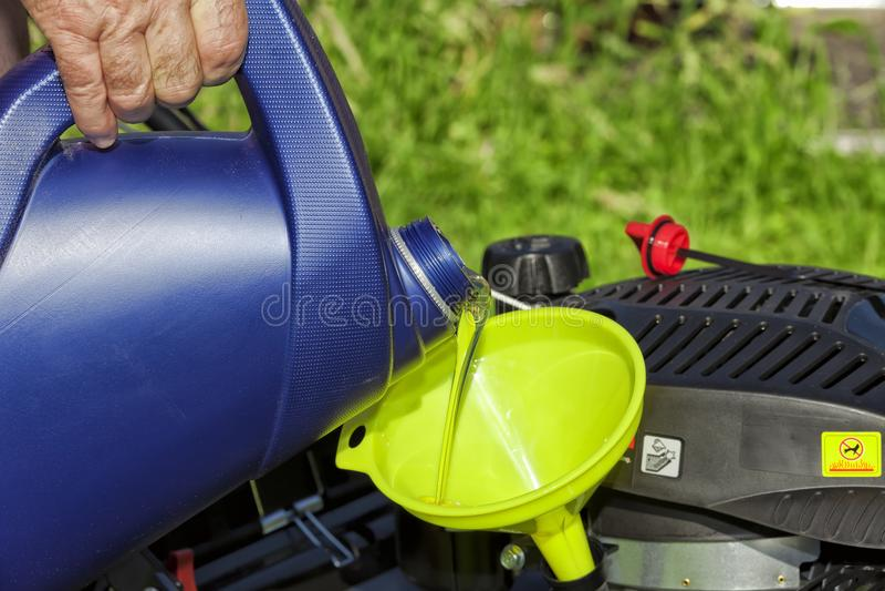Um homem derrama o óleo em seu cortador de grama foto de stock royalty free