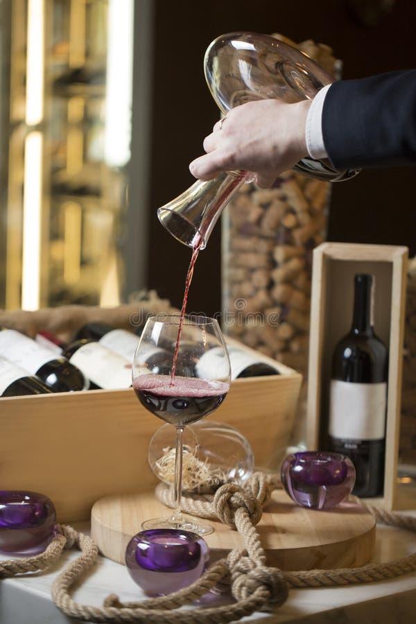Um homem derrama o vinho tinto de um filtro em um vidro, interior do restaurante, decoração: velas nos castiçal, uma corda grossa imagens de stock