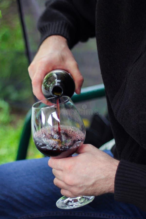 Um homem derrama o vinho tinto em um grande vidro de vidro Piquenique na natureza Foco seletivo imagens de stock royalty free