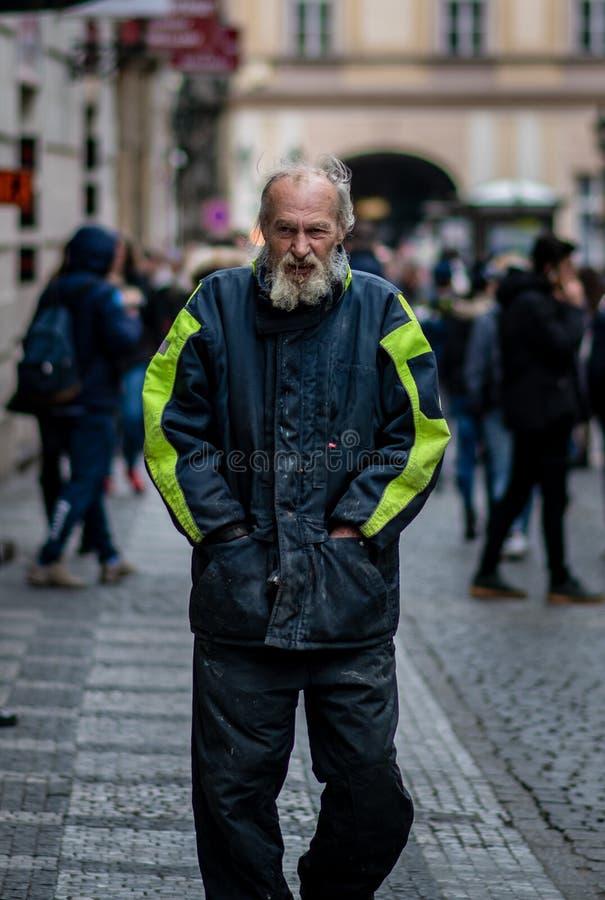 Um homem desabrigado coberto dentro baba e a sujeira anda através das ruas de Praga em um dia de mola frio imagem de stock