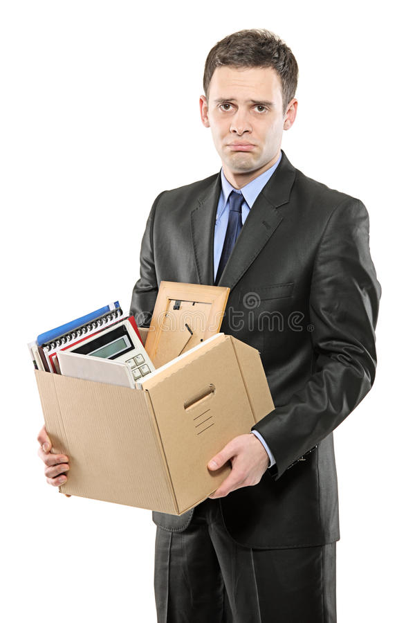 Um homem despedido em um terno que carreg uma caixa foto de stock royalty free