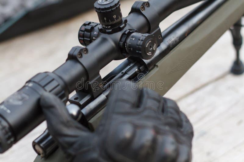 Um homem dispara em um rifle Tiro do rifle com vista ótica fora pelo homem foto de stock