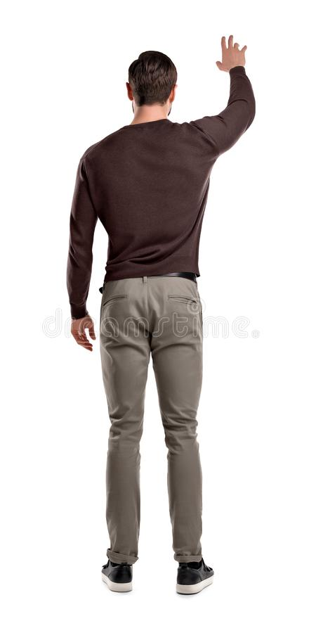 Um homem do ajuste em suportes ocasionais da camiseta em uma vista traseira com o um braço levantado até atrai a atenção a ele foto de stock