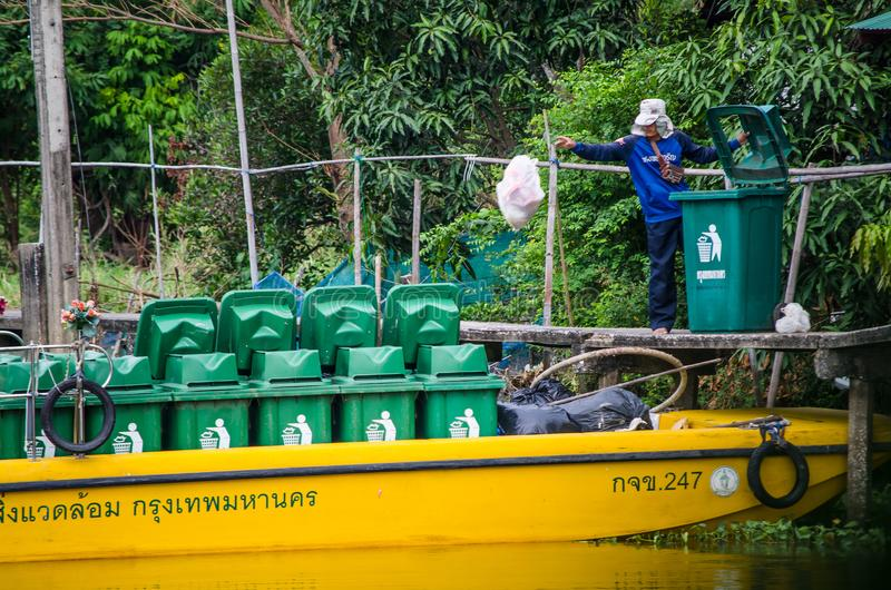 Um homem do escaninho do conselho remove os desperdícios das casas da parte externa perto do canal do ` de Sansab do ` se é enchi imagem de stock