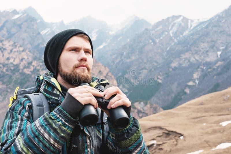 Um homem do moderno com uma barba em um chapéu, em um revestimento, e em uma trouxa nas montanhas guarda binóculos, aventura, tur imagens de stock royalty free