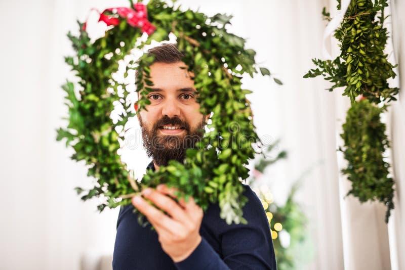 Um homem do moderno que guarda e que olha através de uma grinalda verde no tempo do Natal imagem de stock