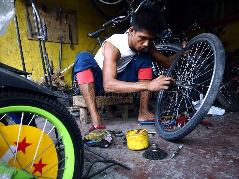 Um homem do reparo da bicicleta fixa um pneu em uma loja de bicicleta fotografia de stock