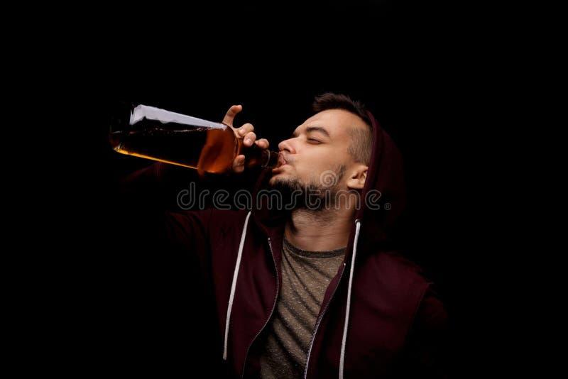 Um homem do risco está bebendo o uísque em um fundo preto Um dependente deprimido do indivíduo no álcool Copie o espaço fotos de stock royalty free
