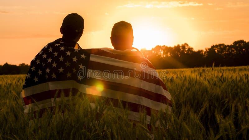 Um homem e seu filho admiram o por do sol sobre um campo de trigo, envolvido na bandeira dos EUA fotos de stock