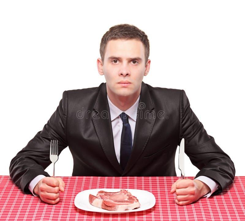 Um homem e uma carne uncooked fotografia de stock