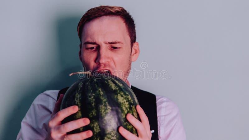 Um homem e uma melancia/menino no terno clássico com uma melancia imagens de stock royalty free