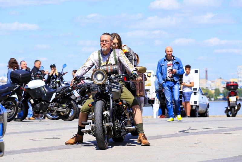 Um homem e uma menina estão sentando-se em uma motocicleta retro Os motociclista em motocicletas caras bonitas abrem a estação fotos de stock