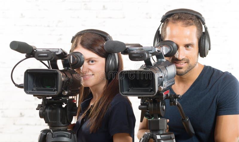 Um homem e uma mulher com câmaras de vídeo imagem de stock royalty free