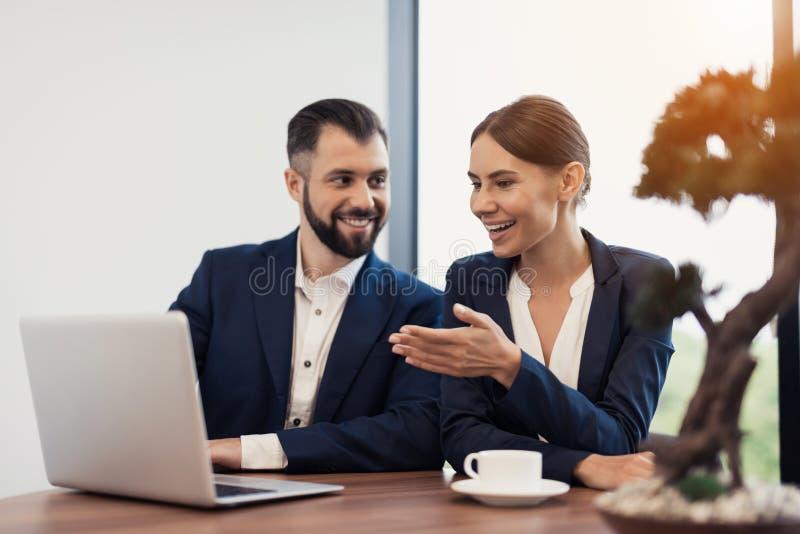 Um homem e uma mulher em ternos de negócio restritos estão discutindo algo ao sentar-se em uma tabela com uma xícara de café fotografia de stock