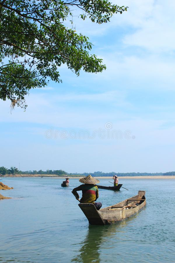 Um homem em um barco perto de uma árvore em um rio em um dia ensolarado brilhante com céus azuis fotografia de stock