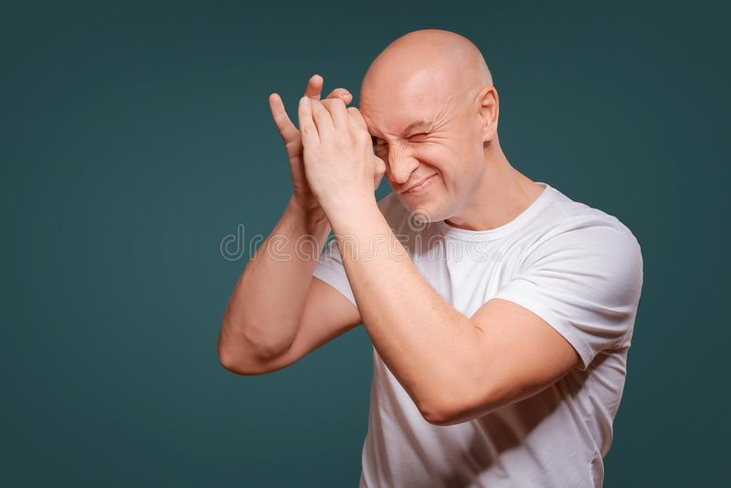 Um homem em um fundo azul em guardar as mãos perto de seus olhos como espreitadelas de um telescópio imagens de stock