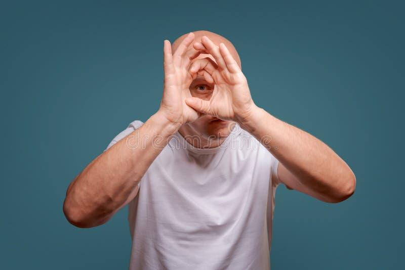 Um homem em um fundo azul em guardar as mãos perto de seus olhos como espreitadelas de um telescópio imagem de stock