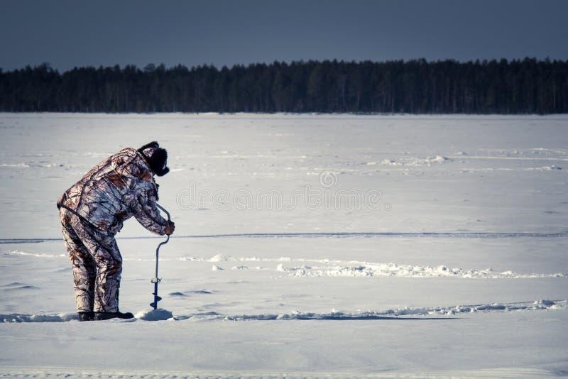 Um homem em um inverno que pesca a broca do gelo do furo de broca fotografia de stock