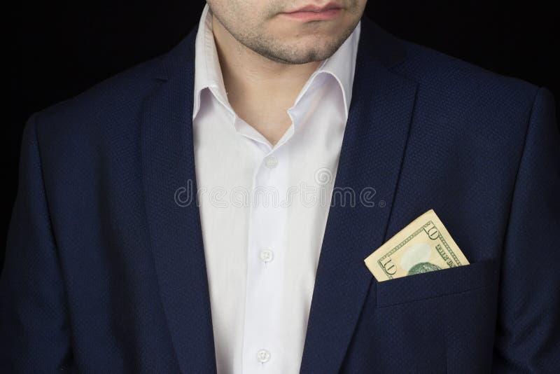 Um homem em um jaque e em uma camisa branca em seu bolso tem dez dólares, um queixo, um close-up fotografia de stock