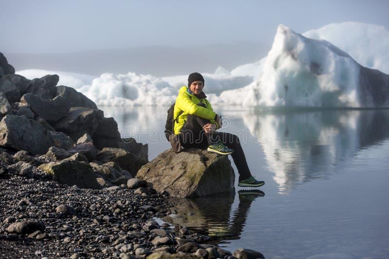 Um homem em um revestimento amarelo, um turista senta-se em uma pedra na costa da lagoa gelada imagem de stock royalty free