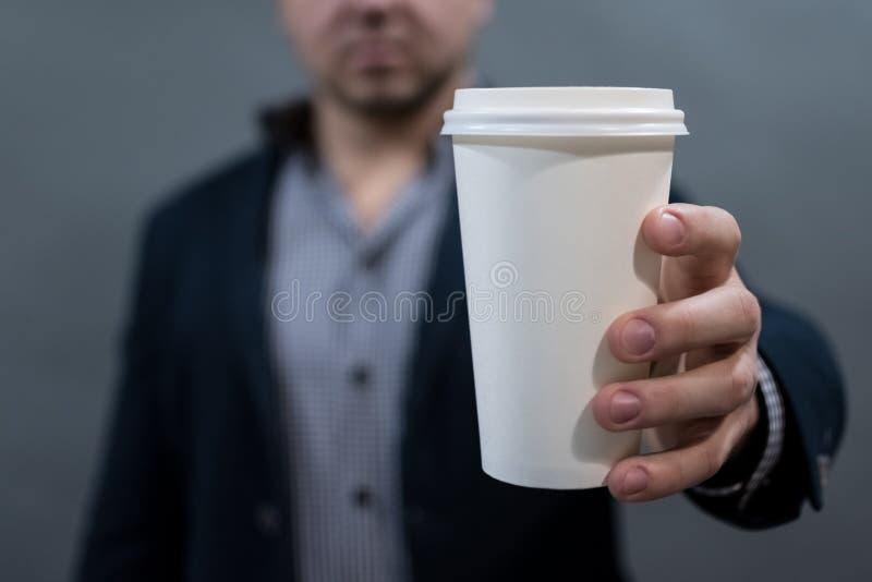 Um homem em um revestimento e em uma camisa que guardam um copo do Livro Branco branco vazio para seu texto fotos de stock