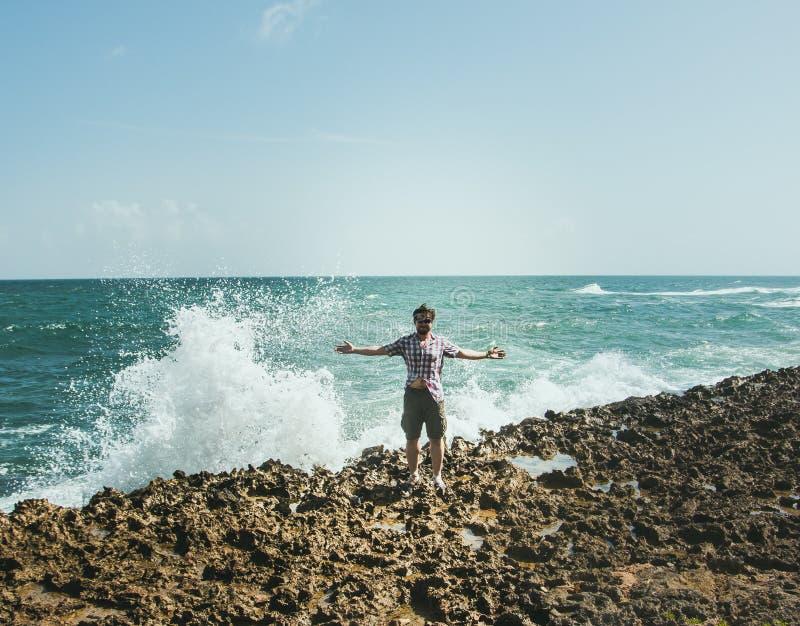 Um homem em suportes dos óculos de sol na costa no pulverizador de deixar de funcionar acena fotografia de stock royalty free