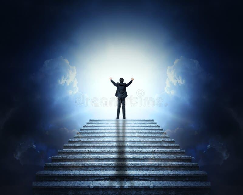 Um homem em um terno com os braços estendido em uma escadaria de pedra às nuvens e à luz Stairway ao céu imagens de stock