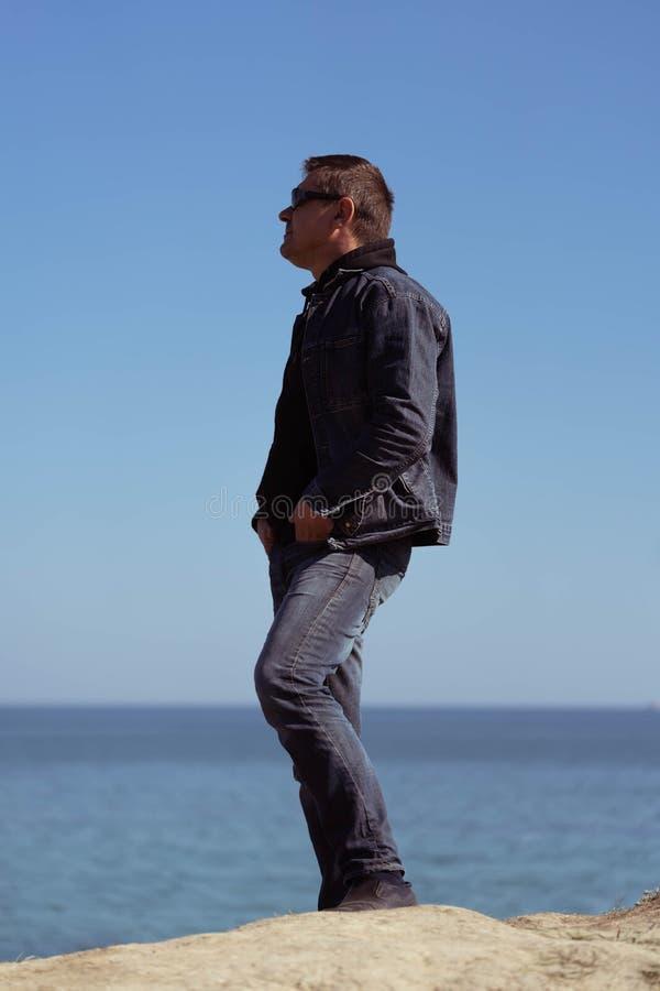 Um homem em um terno da sarja de Nimes no fundo do mar em um dia ensolarado da mola fotografia de stock
