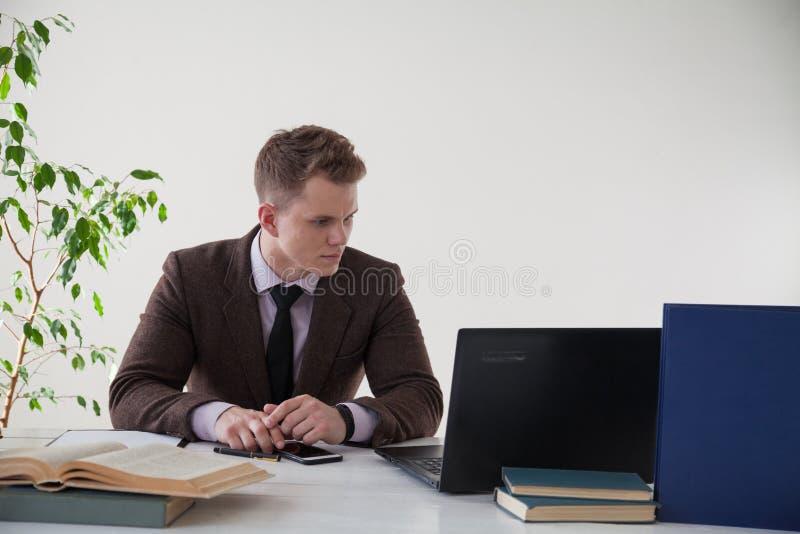 Um homem em um terno de negócio trabalha no computador com os livros no escritório imagens de stock royalty free