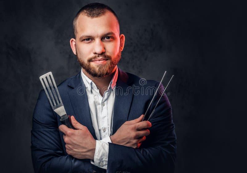Um homem em um terno guarda uma faca do ` s do cozinheiro chefe fotografia de stock royalty free