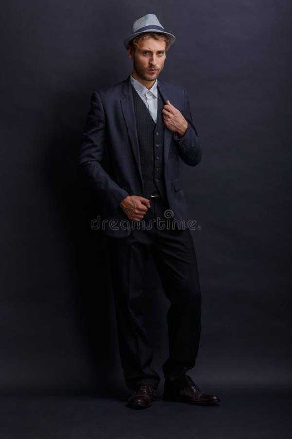 Um homem em um terno preto e o chapéu, suportes com um olhar sério e ajustam seu revestimento nsi mesmo fotografia de stock royalty free