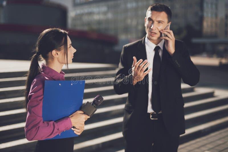 Um homem em um terno preto está dizendo algo no telefone quando um journalista o olhar imagem de stock royalty free