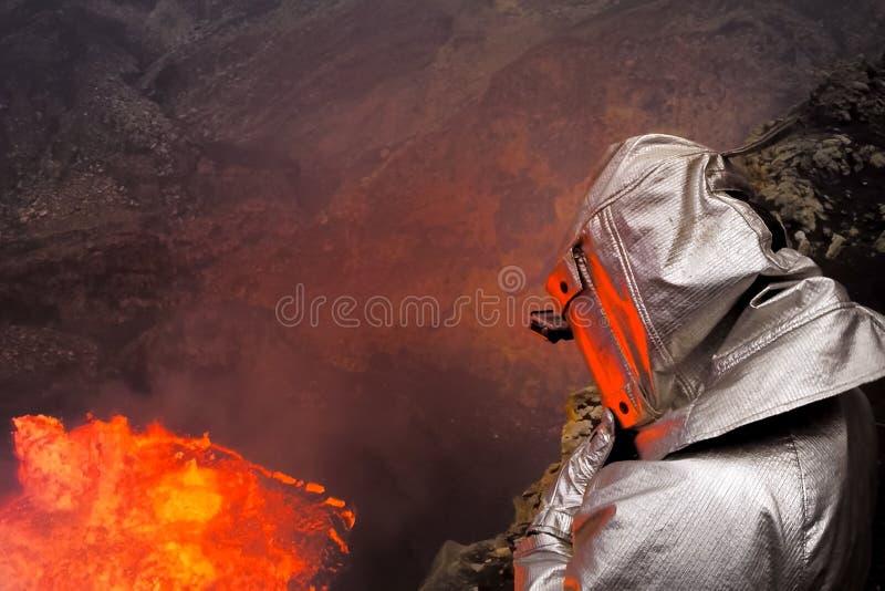 Um homem em um terno protetor perto da boca do vulcão Investigação do vulcão fotos de stock