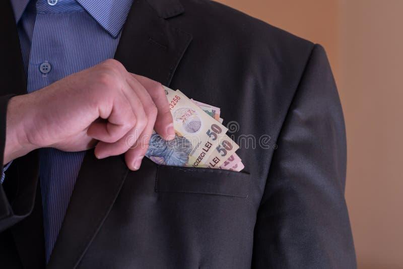 Um homem em um terno retira de suas cédulas do Romanian do bolso fotografia de stock