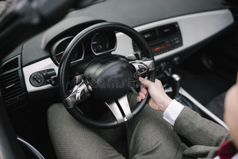 Um homem em um terno senta-se atrás da roda de um carro imagem de stock