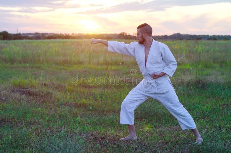 Um homem em um quimono treina o karaté na natureza, um por do sol bonito foto de stock