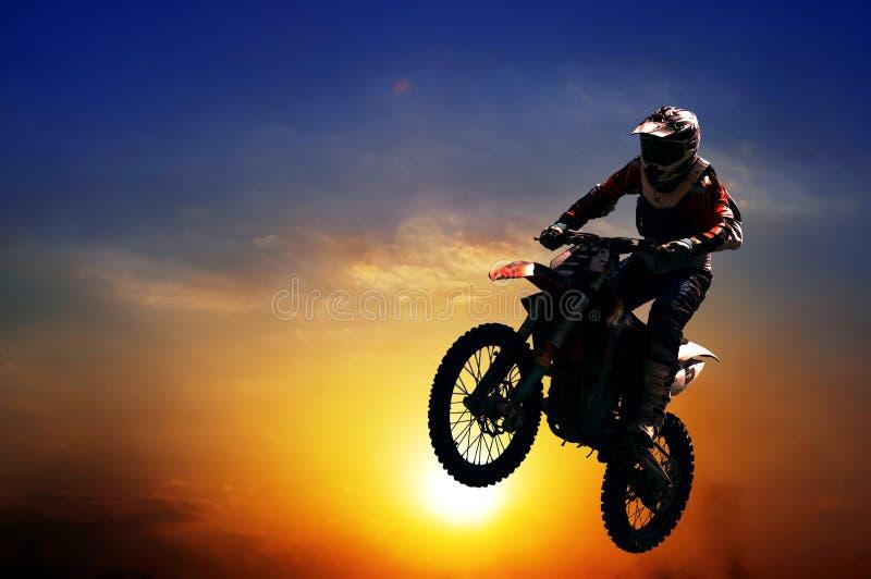 Um homem em um salto da motocicleta imagem de stock