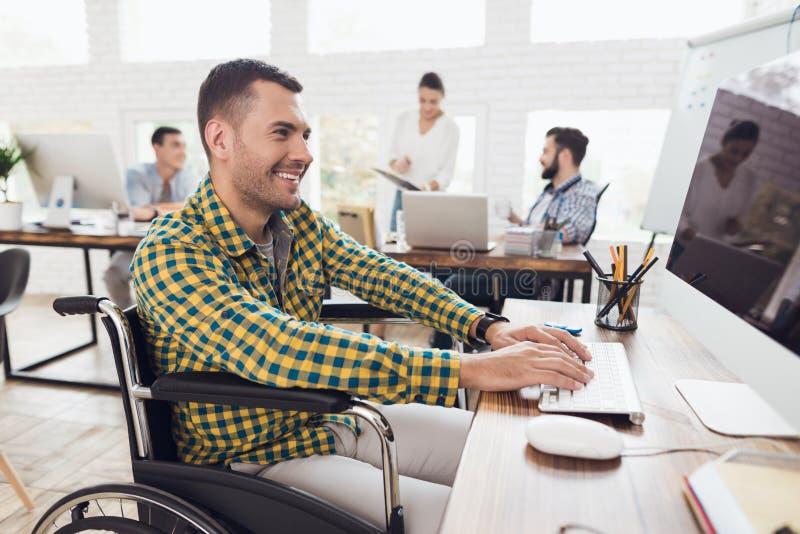 Um homem em uma cadeira de rodas está trabalhando o computador em uma tabela em um escritório moderno imagens de stock royalty free