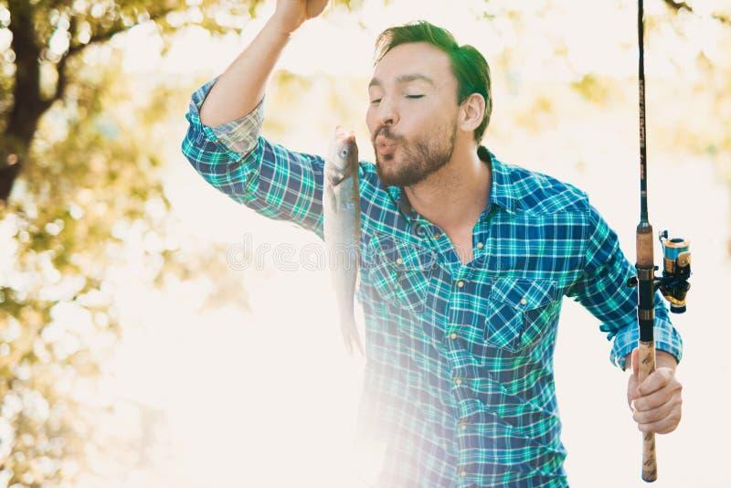 Um homem em uma camisa azul está guardando um peixe em suas mãos, que apenas travou e quer beijar fotos de stock