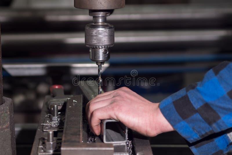 Um homem em uma camisa azul fura um furo nos detalhes em uma pequena empresa foto de stock