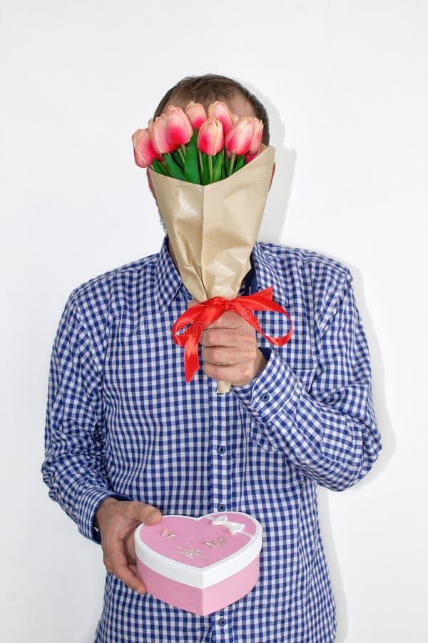 Um homem em uma camisa guarda flores das tulipas na frente de sua cara e guarda para fora uma caixa coração-dada forma em um fund fotos de stock royalty free