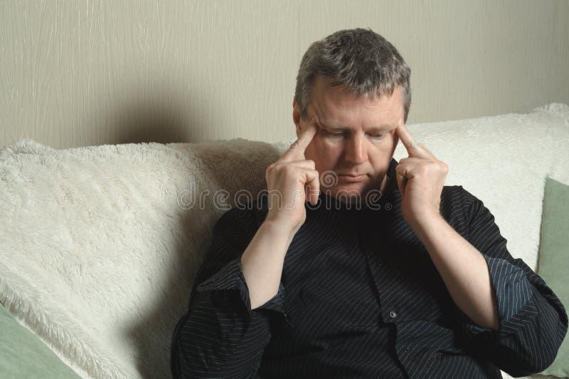 Um homem em uma camisa preta que guarda sua cabeça foto de stock