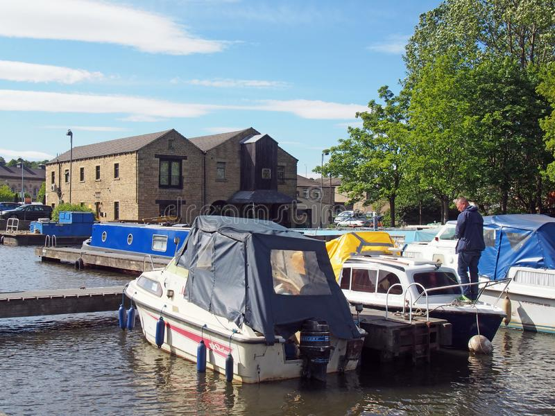 Um homem em uma casa flutuante cercada pelas barcas amarradas na bacia e nas amarrações do brighouse no calder e pelo canal hebbl fotografia de stock